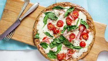 Eine runde Pizza mit liegt auf einem Holzbrett.