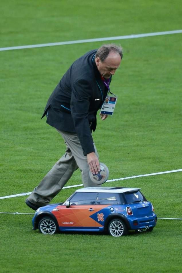 A field assistant puts a discus in a remote control car during the Men's Discus Throw during the London 2012 Olympic Games. How cool is that !!