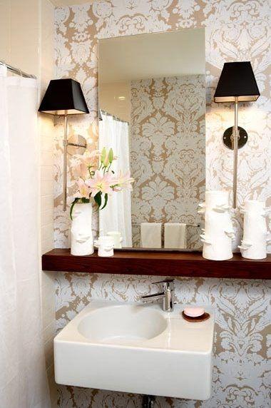 metallic damask wallpaper, floating shelf, polished chrome sconces and sink.