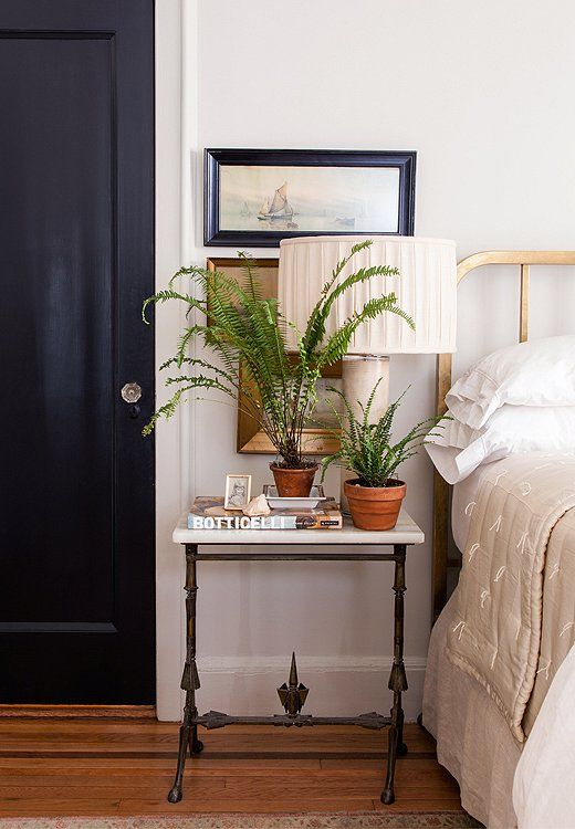 """Smith prefers to paint doors what she calls """"noncolors"""" such as black or taupe rather than white. In the guest bedroom the black door adds a masculine edge to an antique brass bed and marble table."""