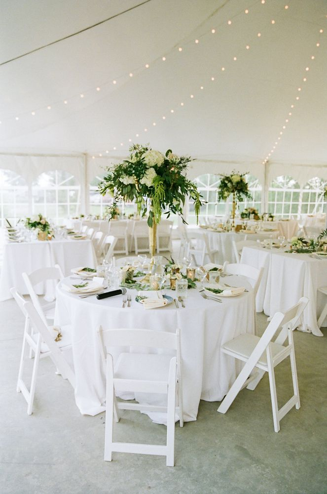 white and sage green reception decor tent wedding reception with a string of lights