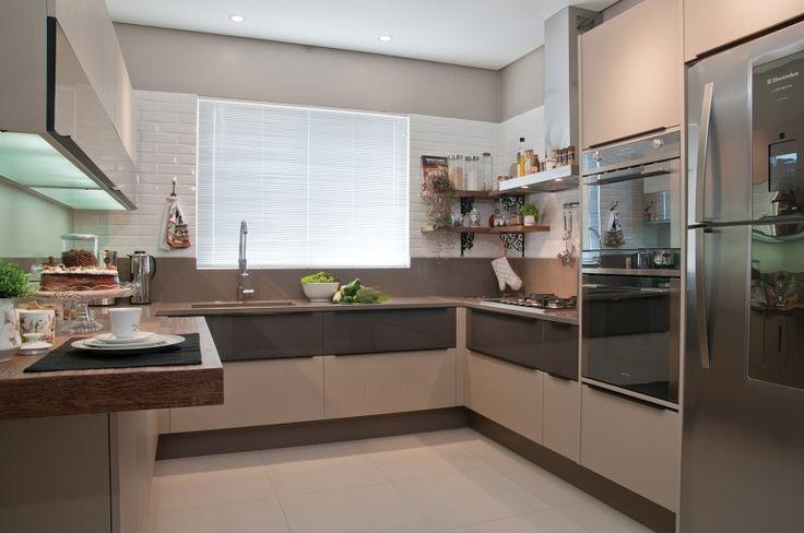 Na cozinha, os tons neutros predominam nas paredes e no mobiliário, que mistura portas com textura e vidro reflexivo bronze, com tampo em silestone.