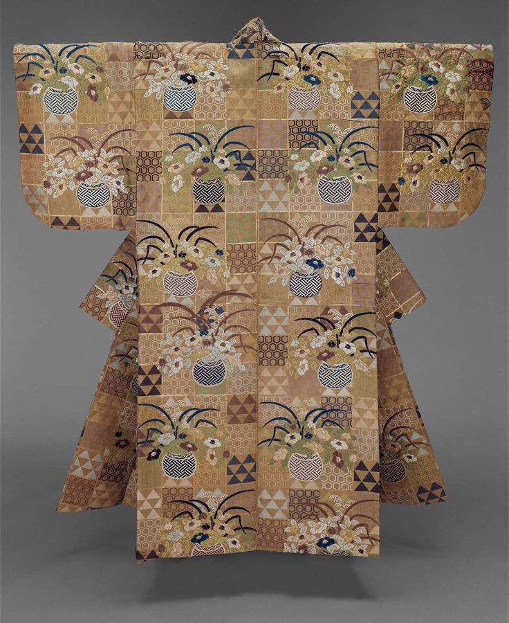 Noh theater robe (karaori), for a female role, with a tan ground and alternating blocks outlined in gold of repeating fish scale (uroko) and tortoiseshell (kikkô-mon) patterns in green, light and dark blue and purple silk and gilt paper and an overall pattern of flower and grass filled baskets in blue, green purple and white silk discontinuous supplementary patterning wefts; blue plain-weave silk lining.