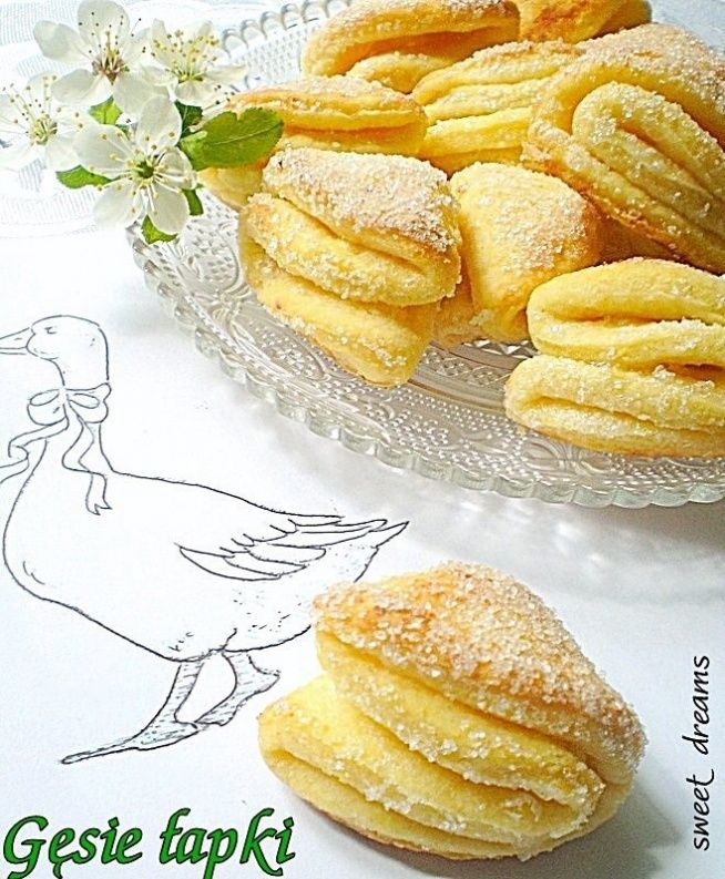 View photo Goose feet Ingredients: - 200 g butter - 200 g cottage cheese semi ankle - 2 cups flour - 2 egg yolks - 2 tablespoons of cold water - 1/2 cup of sugar to rounding Butter freeze, grate, add the crumbled cheese and flour.  Add the egg yolk and water, knead the dough on the uniform, shape into a ball.  The dough wrapped in foil and cooled in a refrigerator for about 1 hour.  After this time, roll out the dough thinly and cut out circles using a glass.  Pour sugar into a bowl and…