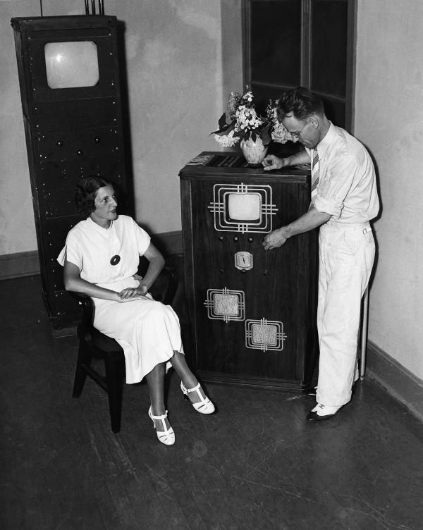 Credit: Image donated by Corbis-Bettmann    In July 1935, Farnsworth Television Laboratories introduced a combination radio and television receiving set that it demonstrated to a group of radio experts and newspaper men. Here, Philo T. Farnsworth shows the set to Mabel Bernstein.