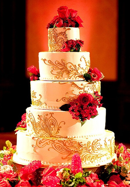 White, 4 tiered cake with gold henna design, and real fresh flowers