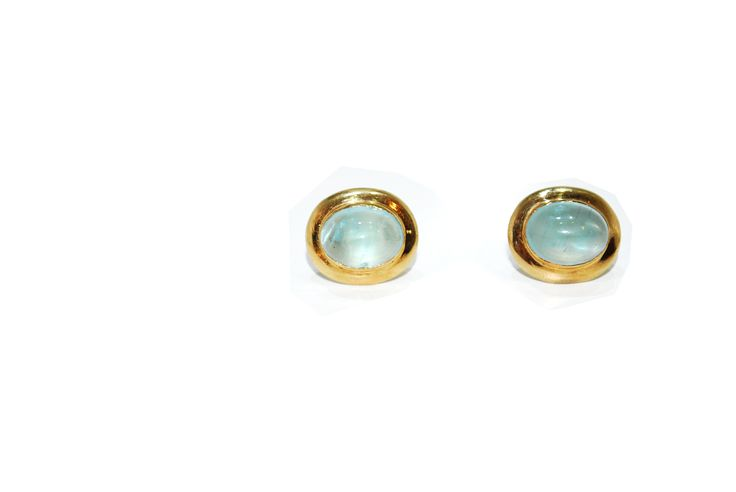 This pair of simple and sleek 9ct gold studs encapsulate a beautifully clear Aquamarine oval cabochon stone.