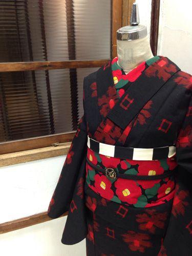 黒に美しく映える赤一色で織り出された、椿のような大輪の花とスクエアの幾何学パターンがモダンなウールの単着物です。