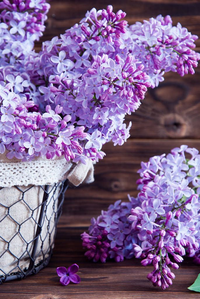 Still life with a blooming branches of lilac in basket on a wooden background