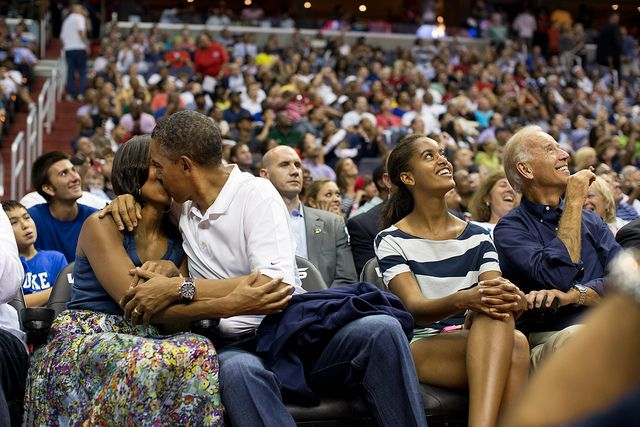 "President Barack Obama kisses First Lady Michelle Obama for the ""Kiss Cam"" while attending the U.S. Men's Olympic basketball team's game against Brazil at the Verizon Center in Washington, D.C., July 16, 2012. Vice President Joe Biden and Malia Obama look up at the jumbotron. (Official White House Photo by Pete Souza)"