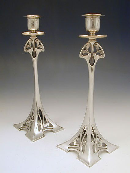 Manufacturer: WMF. Designer: unknown. Description: Pair of silver plate on pewter candlesticks with Art Nouveau floral decoration. Country of Manufacture: Germany. Date: Circa 1906