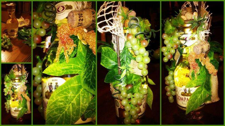 Butelka białego wina ozdobiona sztucznym białym winogrono,korkiem od wina,sztucznymi liśćmi,pestkami dyni oraz jutą