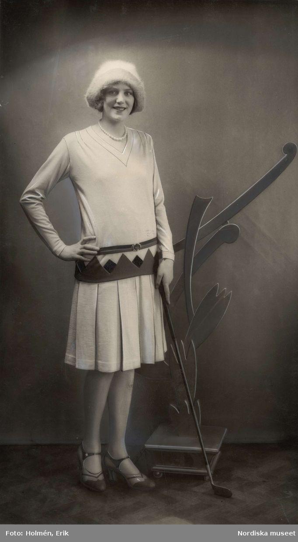 1929. Kvinna iklädd stickad kjol med tillhörande överdel, tvåfärgade skor, huvudbonad och en golfklubba i handen. Foto: Erik Holmén för Nordiska Kompaniet