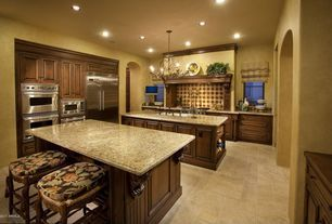 Mediterranean Kitchen with Burnt Umber Chandelier, Complex granite counters, Amarello Ornamental Granite, Large Ceramic Tile