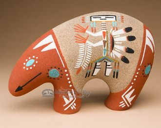 The Navajo Indian artist creates beautiful sand paintings with colorful Native american symbols.