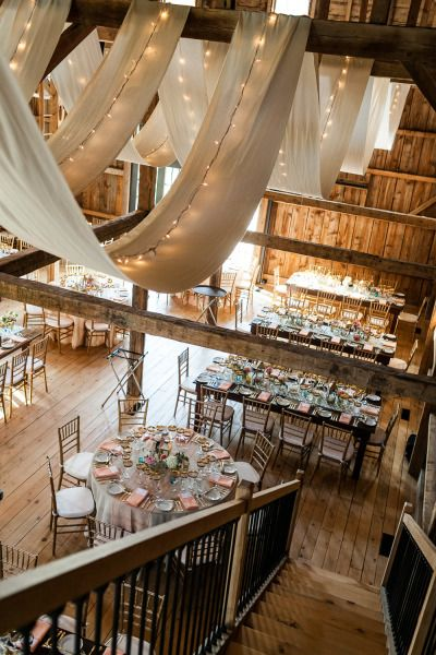 Barn wedding reception decor. I love the drapes and that they mixed round and rectangular tables.