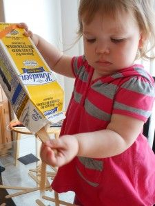 Simple toddler fun! Putting popsicle sticks in an empty milk carton