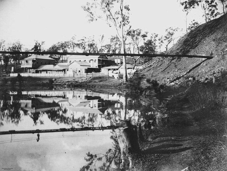 Swing bridge at Mount Morgan, ca. 1900 - This image depicts some of the buildings and houses of Mount Morgan viewed through a swing footbridge in the foreground.