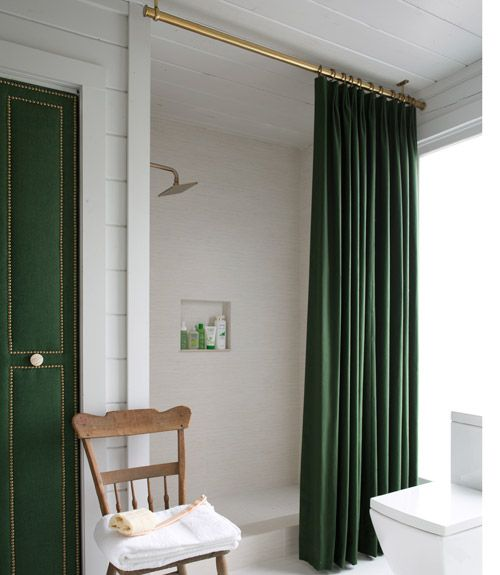 Removing the tiny tub made way for an extra-large shower space. The ceiling-mounted curtain (a custom cotton panel with a waterproof liner) creates the illusion of higher ceilings.   - CountryLiving.com