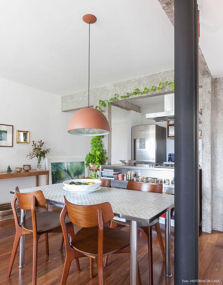 Sala de jantar tem vigas de concreto e tubulação aparente. Na decoração, mesa com mosaicos e cadeiras de madeira.