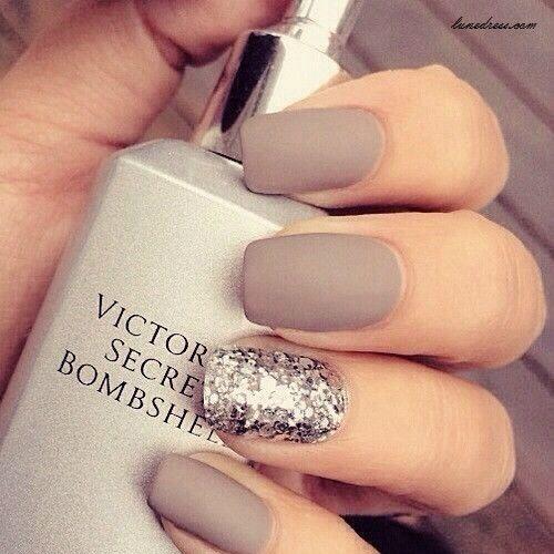 Preciosas uñas en marrón mate, una de ellas adornada con brillos de color plateado.