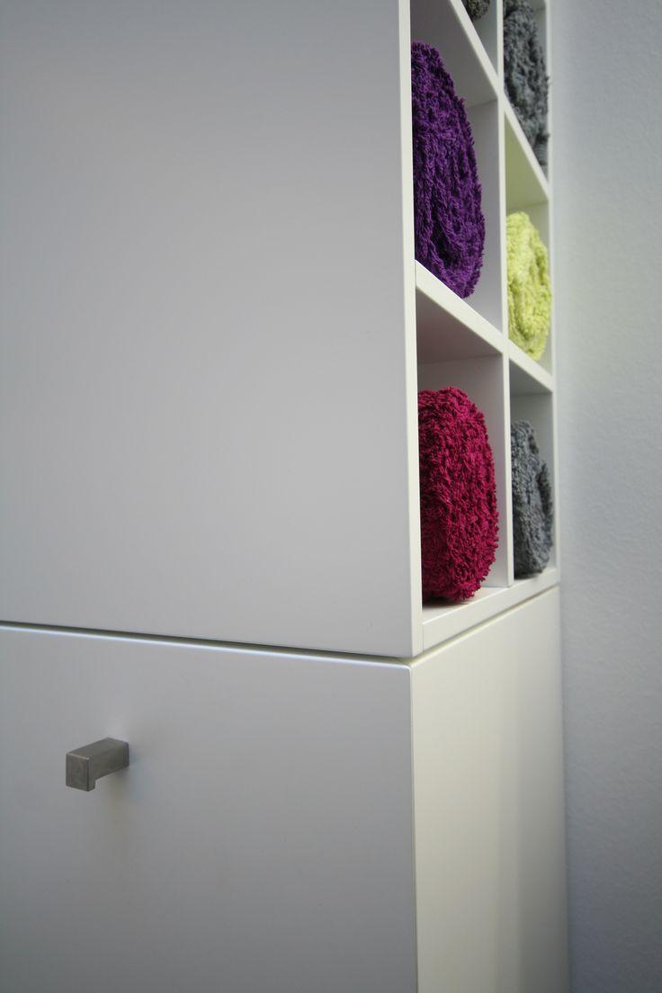 In diesem Regal mit matter Lackoberfläche und Edelstahlgriffen können Handtücher auf stilvolle Weise untergebracht werden.