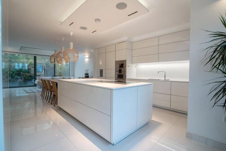This Warendorf kitchen design was all about the sleek clean lines. Totally handleless, glossy glass units in white all operated with electronic servo motors on the drawers and wall units. Blending traditional Danish design wood furniture with the latest in kitchen technology including Gaggenau appliances.