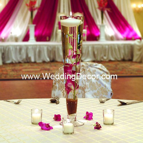 Wedding Centerpiece - fuchsia dendrobium orchids in a pilsner vase with crushed glass and a floating candle - votive candles and orchid blooms as accents