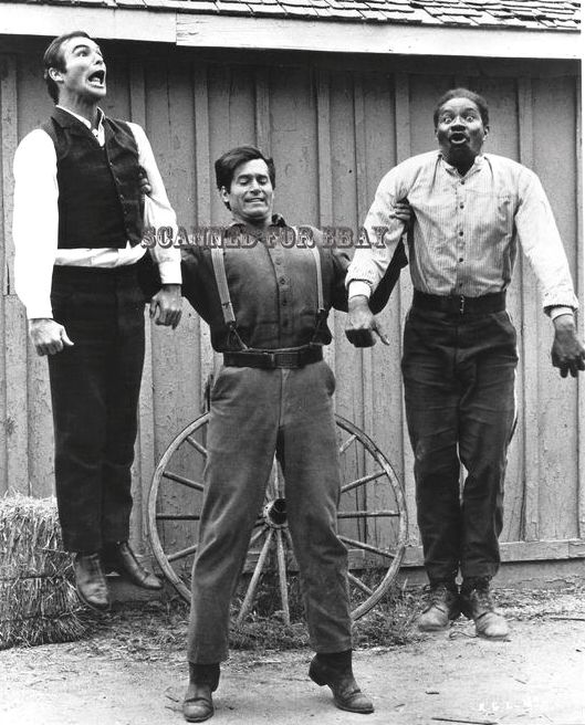 """Clint clowns around on the set with actors (l) Burt Reynolds and (r) Ossie Davis between filming the movie """"Sam Whiskey,"""" 1969."""