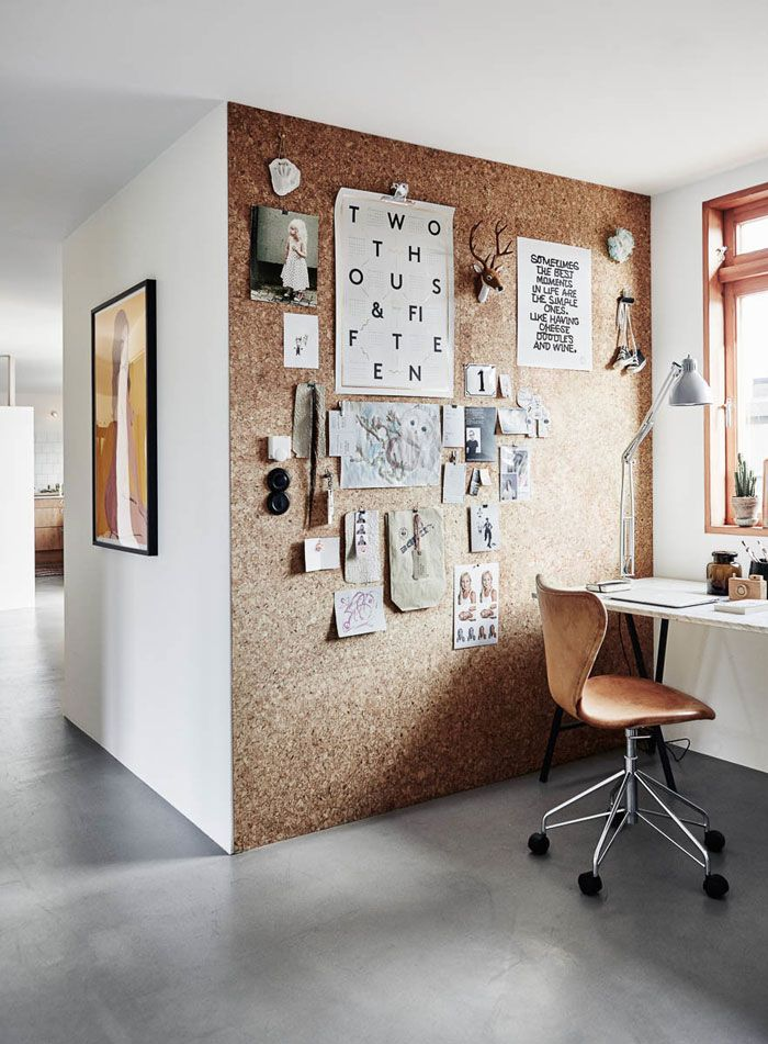 Quirky work space with a cork wall, leather rolling chair, modern white desk, white walls and concrete floors | Photos by Tina Hellberg for Elle Decoration