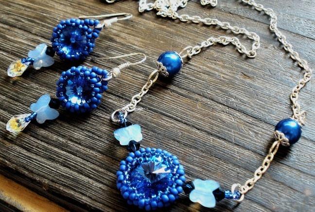 Swaeovski krystal v jasne modrom odtieni je obšitý prvotriednym japonským rokajlom , ktorý plynule prechádza do swarovski krystalov v tvare motýľov v opálovo modrom odtieni a swarovski bicone v temne modrom odtieni. Nakoniec náhrdelnik dotvárajú voskované perly s filigránovými kaplíkmi.  Náušničky sú zhotovené z rovnakých materiálov, na koncoch dotvorené so swarovski kvapkou s aurora borealis pokovom, ktorý dodáva nádherné odlesky