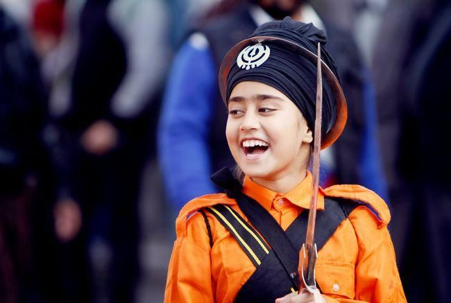A young India Sikh girl smiles as she participates in a religious procession of the birth anniversary of Guru Gobind Singh in Jammu, India. #Sikh #India