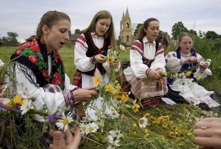 Belarussian women make wreaths during the Ivana Kupala festival near the town of Rakov, some 45 km (28 miles) northwest of Minsk, July 6, 2009. The traditional festival celebrates the summer solstice with overnight festivities such as people singing and dancing before jumping over campfires, as they believe it will purge them of their sins and make them healthier.