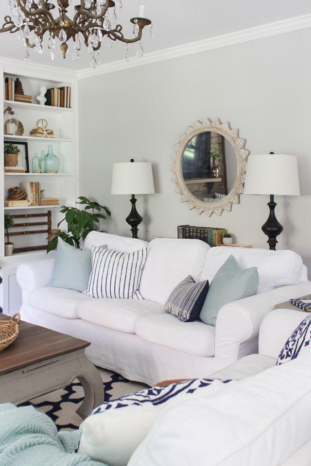 sofás slipcovered blanco con aqua y azul marino acentos en salón de verano