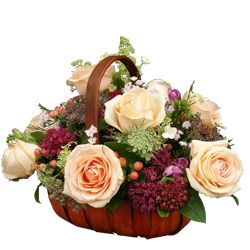 This exquisite peach rose basket contains seasonal flowers and foliage.