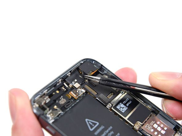 1. Vipp kameraets gummilokk ut av festeklemmen med en pinsett og trekk det mot utsiden av bakdekselet.