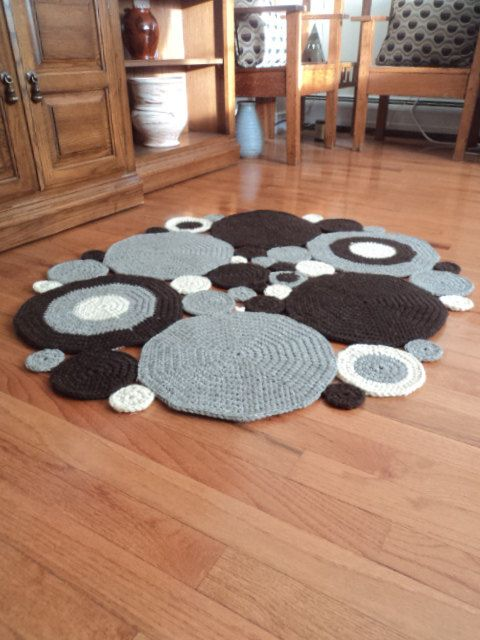 REDUCED PRICE:  Original price was $140..00  Reduced price is $110.00    This area rug is made up of many circles that were sewn together. The fiber of this rug is UN-dyed wool. Cream, oatmeal grey, and dark brown. I have added a non-slip mat to the larger circles. This will keep your rug where you place it. Nothing worse than a rug slipping out from under you. My son tested the gripping factor and it held up rather well with his running around.    Size: measured at the widest. 2 feet, 10…