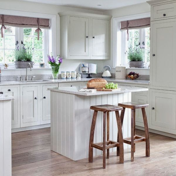 Love this small white cottage farmhouse kitchen.  The gray countertops give a little offset to all the white and the curtain valances give a little pop of color.  Good use of a small island in this tiny kitchen.