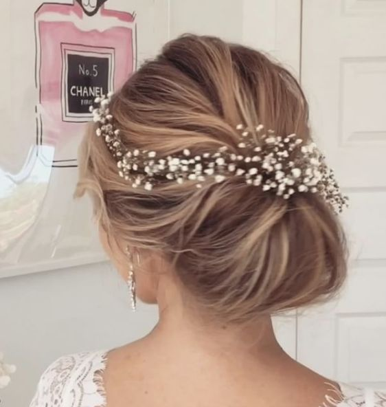 Sleek low bun wedding hairstyle with elegant white hairpiece; Featured Hairstyle: Ulyana Aster