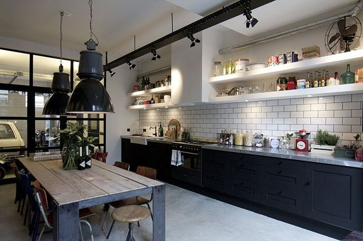 Industrial chic kitchen with black cabinets and white shelves with large vintage industrial lights, white subway tiles