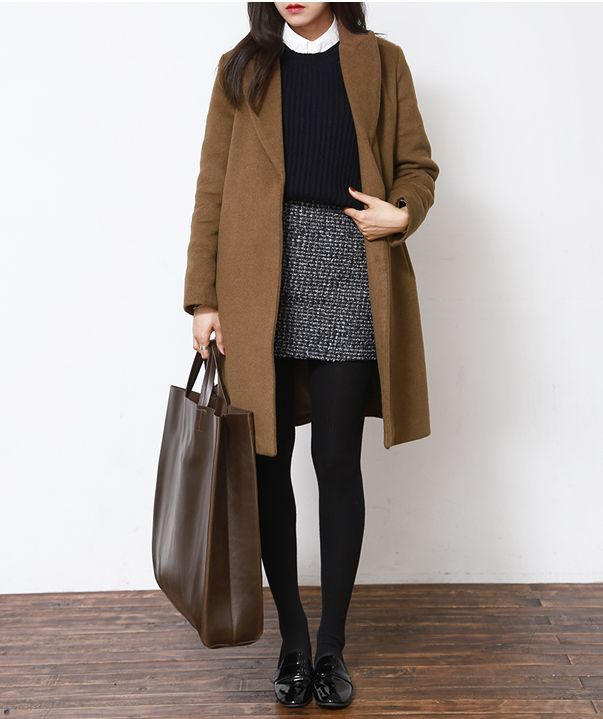 White button-up blouse, black sweater, black and white mini skirt, black tights, camel coat, black oxford flats