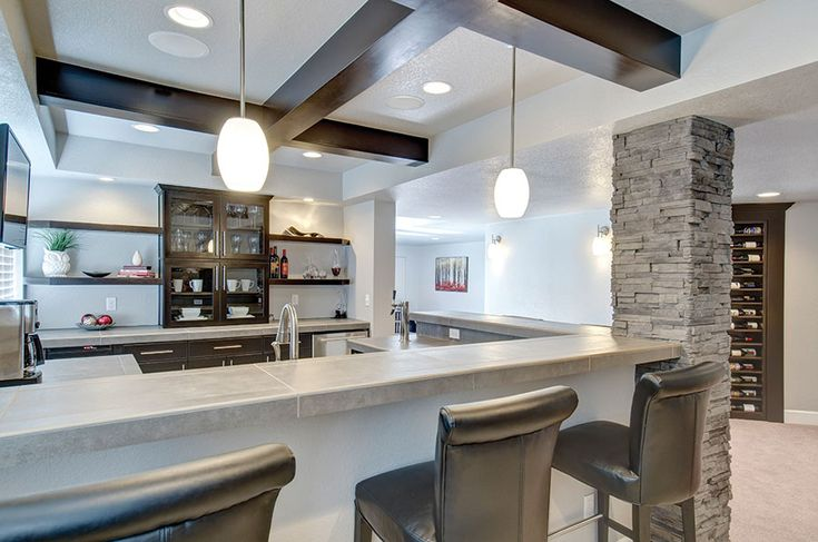 The basement bar is anchored on one side by stacked stone column. Large wood beams on the ceiling complement the dark custom cabinetry.