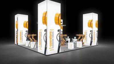 298 Industrieroboter l operators   | Einladender Messestand für ein Hersteller von Industrierobotern.   Die hohen, rahmenlos bedruckten Leuchtsäulen sind ein Blickfang und machen den gr...