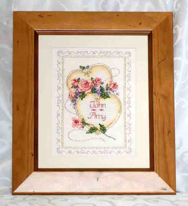 Entwined Hearts Wedding Embroidery. This gorgeous design of two hearts entwined and scattered about with flowers will make the  perfect gift for the wedding couple. Personalised with the names of the Bride and Groom and their Wedding date.
