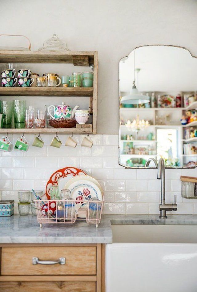 Shabby chic farmhouse accent ideas for your kitchen include colorful glassware and dishes, rustic shelving and hooks for mismatched tea cups.