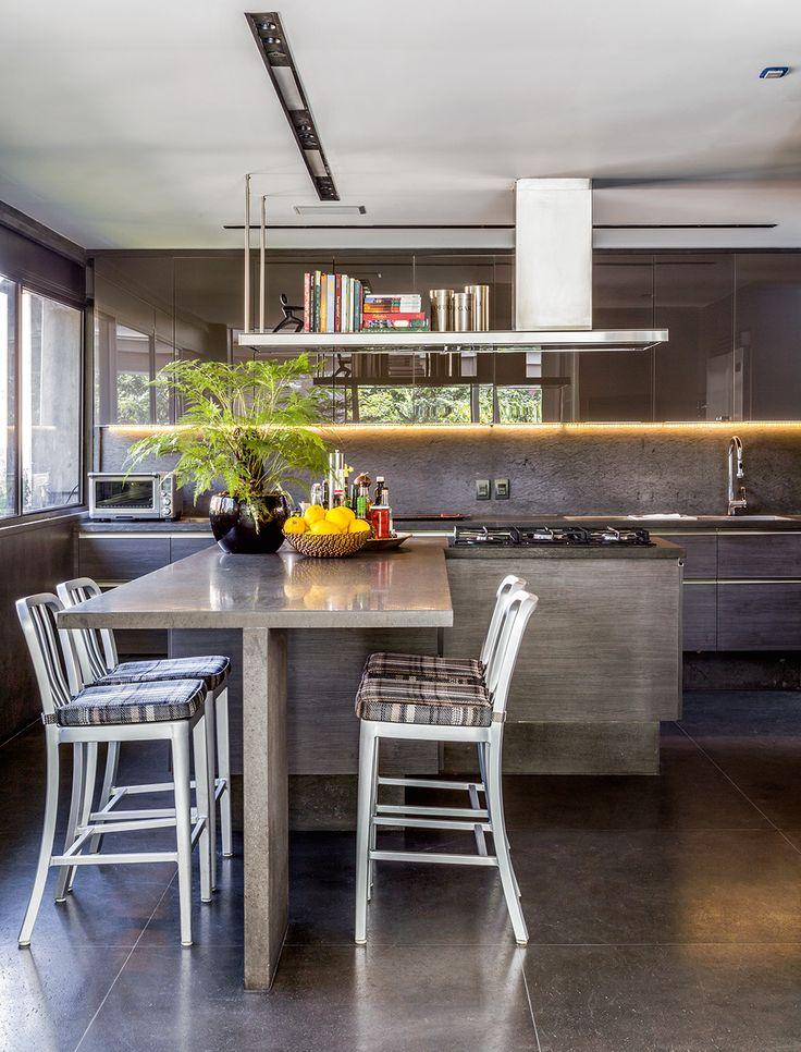 Na cozinha, piso, paredes e bancadas são de mármore black travertino (MSA Marmoraria). Para sentar, cadeiras de aço escovado da Montenapoleone.