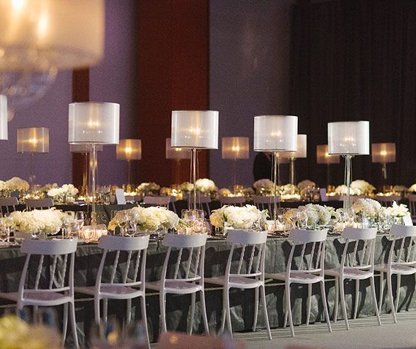 A long banquet table is punctuated with low floral centerpieces and tall glass candelabras.