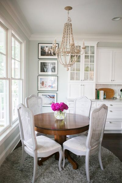 French Inspired Dining Room Features A Wood Beaded Chandelier Which Hangs Over Round Table Lined With Gray Cane Back Chairs Atop