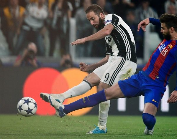 Barcelona's defender Gerard Pique (R) fights for the ball with Juventus' forward from Argentina Gonzalo Higuain during the UEFA Champions League quarter final first leg football match Juventus vs Barcelona, on April 11, 2017 at the Juventus stadium in Turin.  / AFP PHOTO / MIGUEL MEDINA