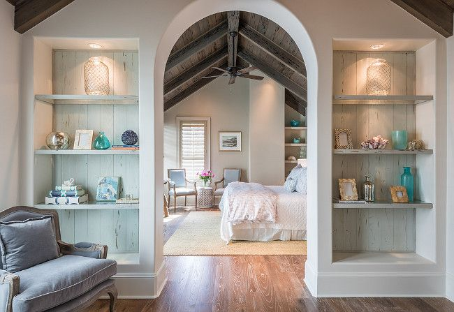 Arched Bedroom sitting Area. An arched doorway to a bedroom is flanked by built-in bookcases lined with distressed plank boards. #Arched #Bedroom #SittingArea Old Seagrove Homes.